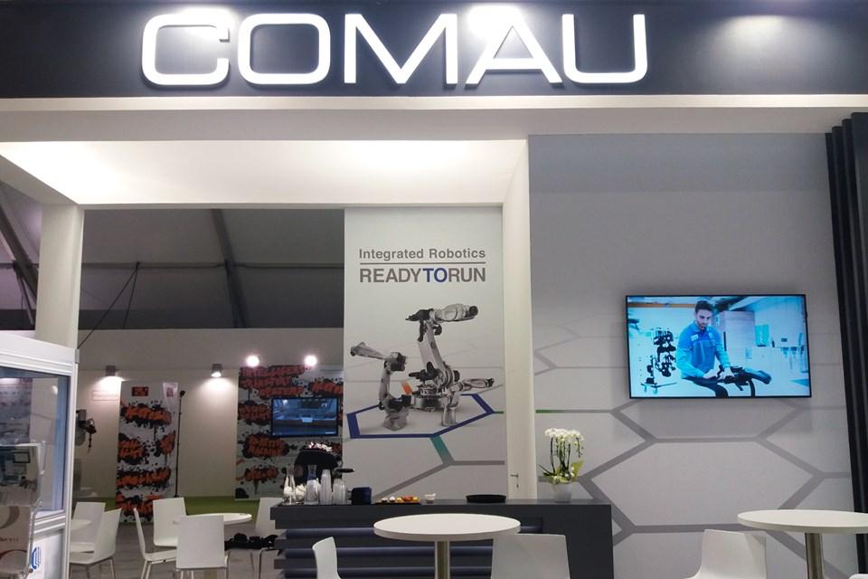 Uno stand della Comau in fiera con i robot